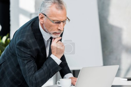 pensive handsome middle aged businessman in suit and glasses looking at laptop in office
