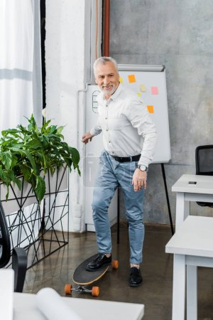 Photo for Cheerful handsome middle aged businessman putting leg on longboard in office - Royalty Free Image