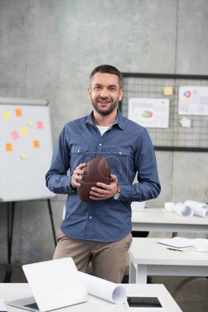 Photo pour Homme d'affaires beau sourire tient ballon de football américain et en regardant la caméra dans le Bureau - image libre de droit