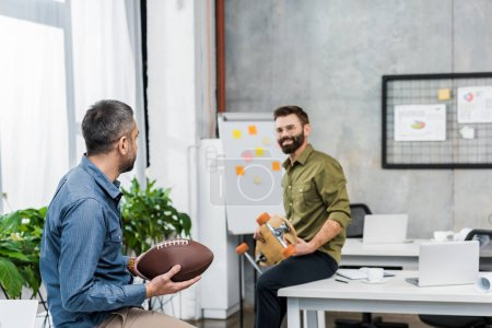 smiling businessmen looking at each other and holding american football ball and longboard in office