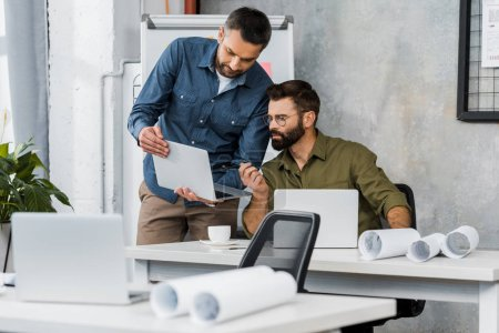 two handsome businessmen looking at laptop in office, blueprints on tabletops