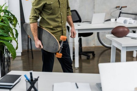 Photo for Cropped image of businessman standing with longboard in office - Royalty Free Image