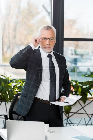 handsome middle aged businessman touching glasses and looking at camera in office