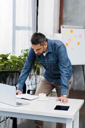 Photo pour Bel homme d'affaires appuyé sur la table et regardant la table dans le bureau - image libre de droit