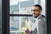handsome businessman in suit and glasses standing near window with cup of coffee and looking at camera in office