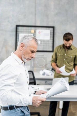 handsome businessmen looking at blueprints in office