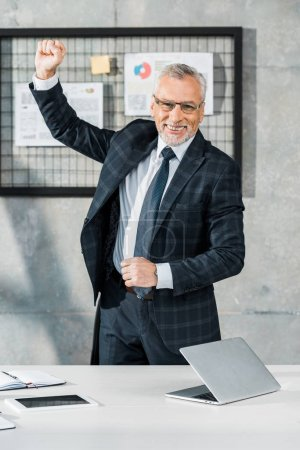 happy handsome middle aged businessman gesturing and looking at camera in office