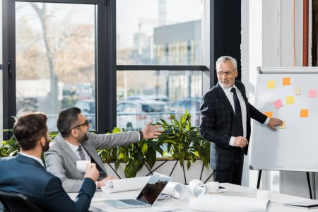 smiling handsome mature businessman pointing on flipchart in office