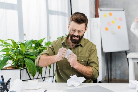 angry businessman tearing paper at table in office