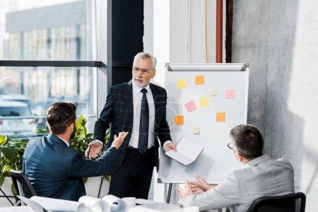 Photo pour Discussion de beaux hommes d'affaires au cours de la réunion dans le Bureau - image libre de droit