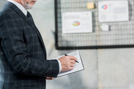 Photo for Cropped image of middle aged businessman in suit writing something to notebook in office - Royalty Free Image