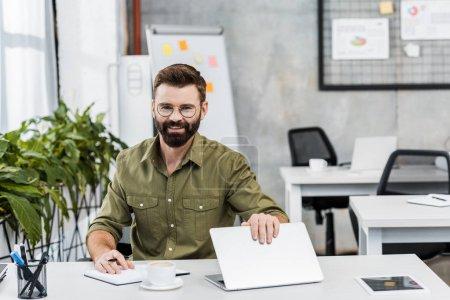 Photo pour Homme d'affaires beau et souriant assis à table avec ordinateur portable et ordinateur portable et regardant la caméra dans le bureau - image libre de droit