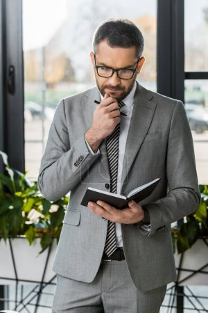 handsome pensive businessman in suit and glasses looking at notebook in office