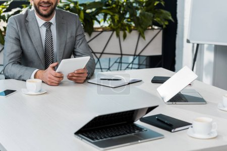 Photo for Cropped image of businessman holding tablet at table in office - Royalty Free Image
