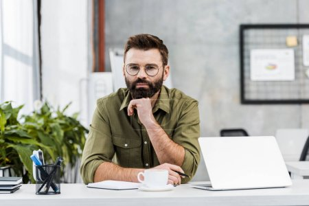 handsome bearded businessman resting chin on hand and looking at camera in office