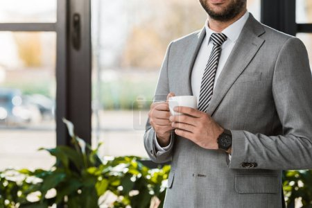 Photo for Cropped image of businessman holding cup of coffee in office - Royalty Free Image