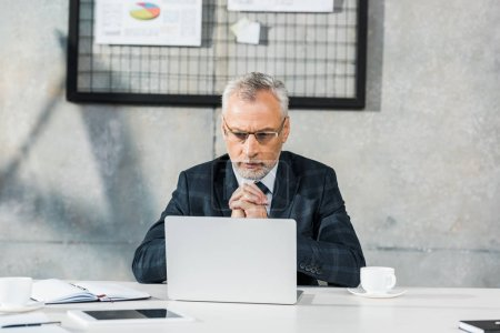 pensive handsome middle aged businessman looking at laptop in office