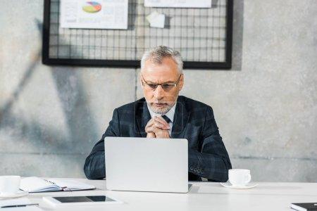 Photo pour Songeur beau milieu âgé homme d'affaires en regardant ordinateur portable au bureau - image libre de droit