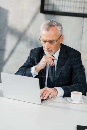 high angle view of pensive handsome middle aged businessman looking at laptop in office