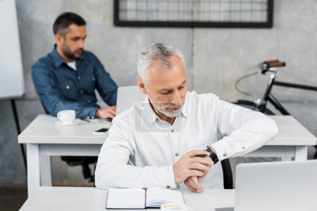 handsome businessman checking time on wristwatch in office