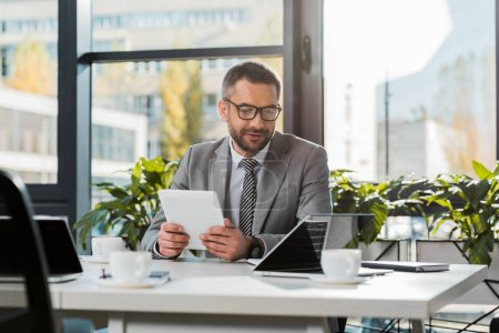 wesoły przystojny biznesmen trzymając tablet i patrząc na laptopie w biurze