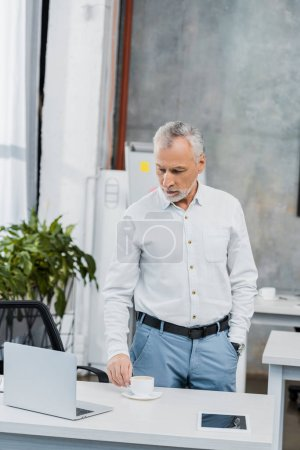 pensive handsome middle aged businessman standing and looking at laptop in office