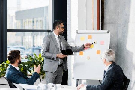 Photo pour Beaux hommes d'affaires lors de réunion avec présentation du projet au bureau - image libre de droit
