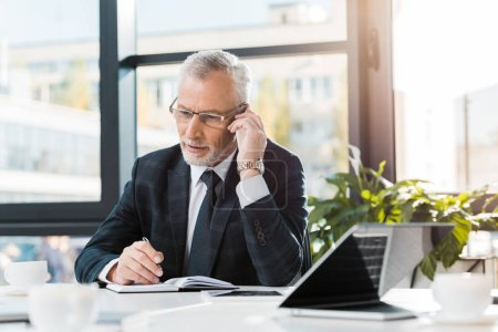 Photo for Handsome middle aged businessman sitting at table and talking by smartphone in office - Royalty Free Image