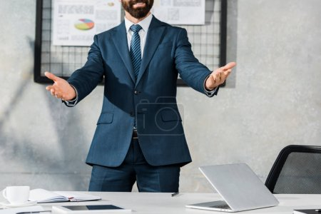 cropped image of businessman gesturing and standing with open arms in office