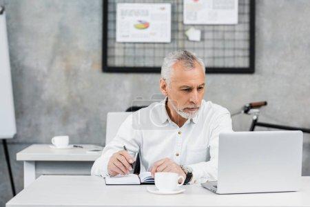 Photo pour Sérieux beau milieu d'âge homme d'affaires tenant stylo et regardant ordinateur portable dans le bureau - image libre de droit