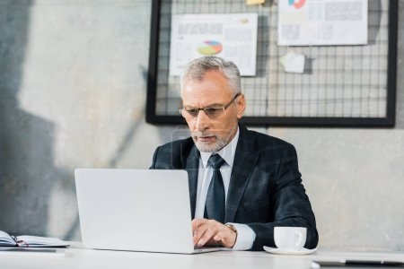 pensive handsome middle aged businessman in glasses working at laptop in office