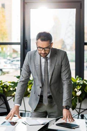 Foto de Hombre de negocios guapo en traje y gafas, apoyado en la mesa en la oficina - Imagen libre de derechos