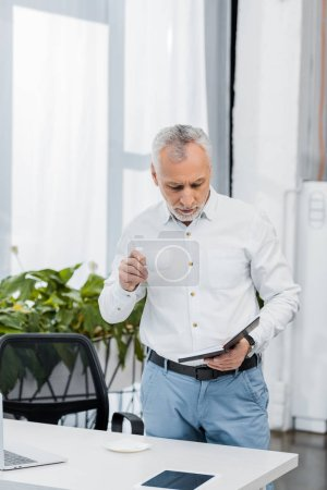 Photo for Handsome middle aged businessman holding cup of tea and looking at notebook in office - Royalty Free Image
