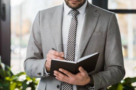 Photo pour Image recadrée de l'homme d'affaires en costume écrit quelque chose à portable dans le bureau - image libre de droit