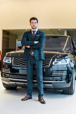 low angle view of businessman in eyeglasses posing with crossed arms near black automobile