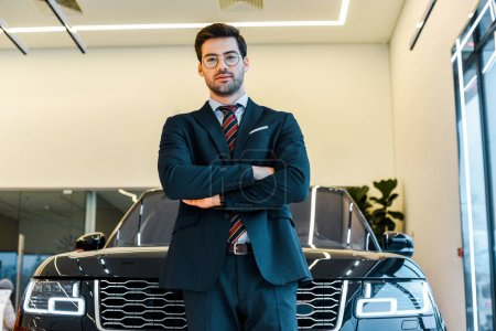Photo for Low angle view of businessman in eyeglasses posing with crossed arms near black automobile - Royalty Free Image