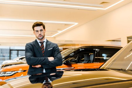 Photo for Confident businessman in eyeglasses posing with crossed arms near black automobile - Royalty Free Image