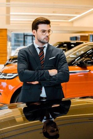 Photo pour Homme d'affaires grave en lunettes posant avec les bras croisés près automobile noir - image libre de droit