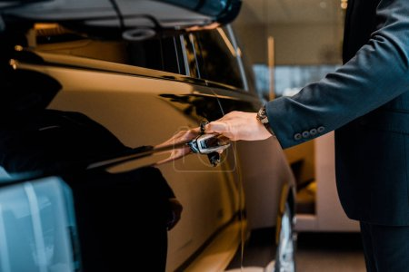 cropped image of businessman in suit opening door of black automobile