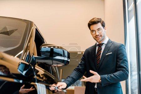 Photo pour Sourire de concessionnaire automobile mâle dans lunettes pointant au noir automobile au salon de l'automobile - image libre de droit