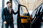 confident businessman in eyeglasses opening door of black automobile