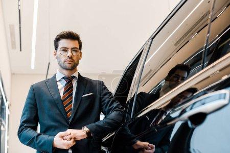 Photo pour Vue à angle bas de l'homme d'affaires dans les lunettes posant près de l'automobile dans le salon de voiture - image libre de droit