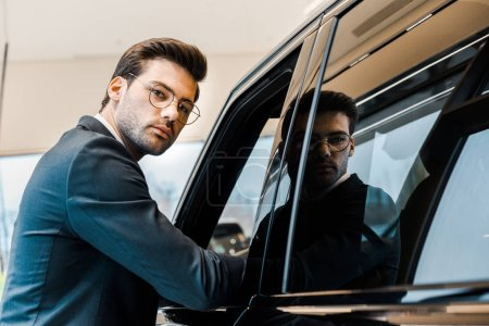 young businessman in eyeglasses posing near automobile in car salon