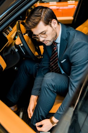 Photo for High angle view of businessman in eyeglasses adjusting trousers in luxury car - Royalty Free Image