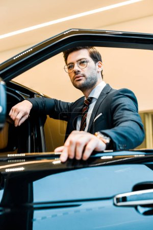 low angle view of confident businessman in eyeglasses posing near automobile in car salon