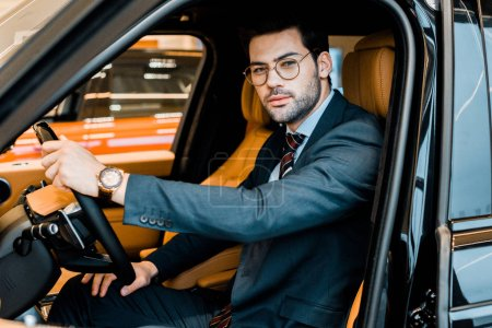 Photo for Stylish businessman in eyeglasses looking at camera while sitting in luxury car - Royalty Free Image