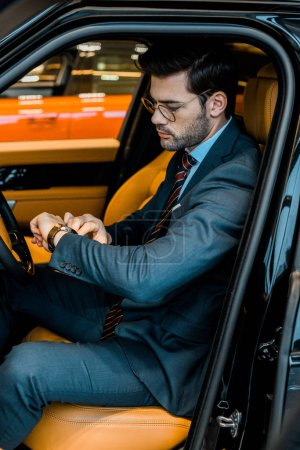 handsome businessman in eyeglasses checking watch in luxury car