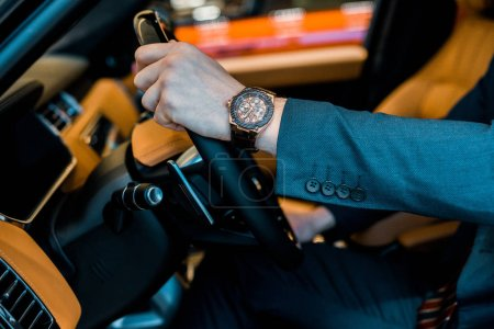 cropped image of businessman with luxury watch sitting in automobile