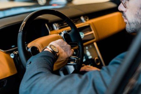 Photo pour Vue partielle de l'homme d'affaires vérifier montre en voiture de luxe - image libre de droit