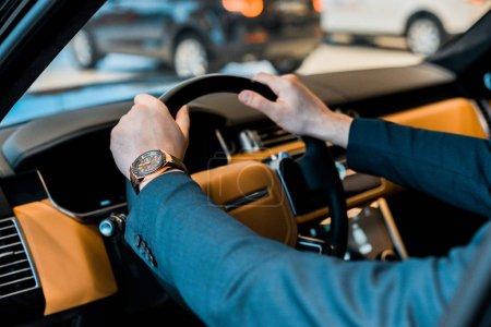 Photo pour Image recadrée de l'homme d'affaires avec montre de luxe assis dans l'automobile - image libre de droit